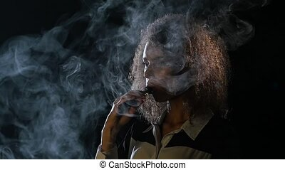 African american woman smokes an electronic cigarette and lets smoke out of her mouth. Black background. Slow motion
