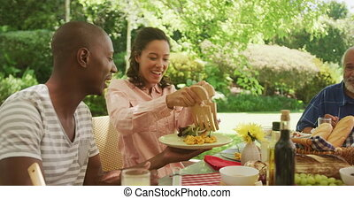 African American woman spending time in garden, sitting at a dinner table with her family, putting food on a plate, in slow motion.