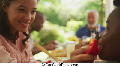 African American woman spending time in garden, sitting at a dinner table with her family, wiping her son face, in slow motion.