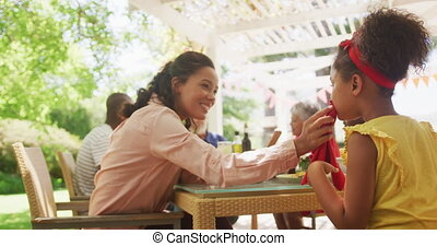 African American woman spending time in garden, sitting at a dinner table with her family, wiping her daughter face, in slow motion.