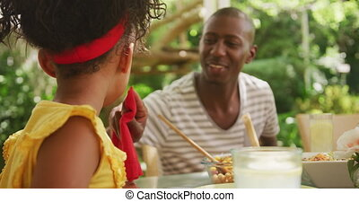 African American woman spending time in garden, sitting at a dinner table with his family, wiping his daughter face, in slow motion.
