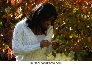 African-American woman staring at leaves