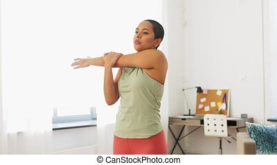 african american woman stretching arm at home - sport and ...