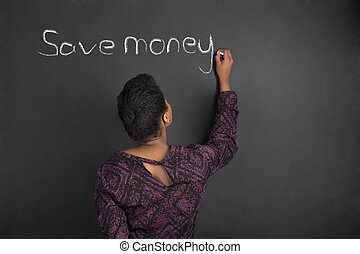 "African American woman teacher writing ""save money"" on chalk black board background"