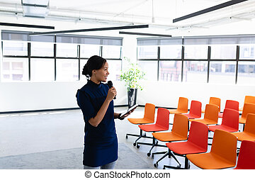 African American woman training herself in a conference room