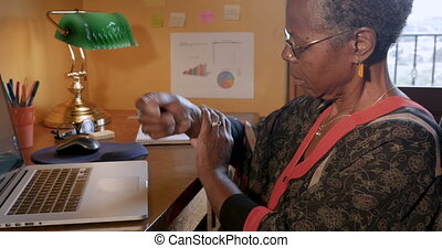 African American woman typing on a computer stops because of wrist joint pain