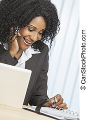 African American Woman Using Cell Phone & Laptop in Office