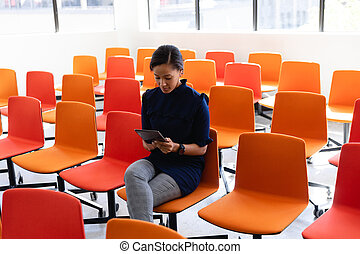 African American woman using digital tablet in a conference room