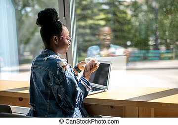 African american woman using laptop while sitting at cafe, back view.