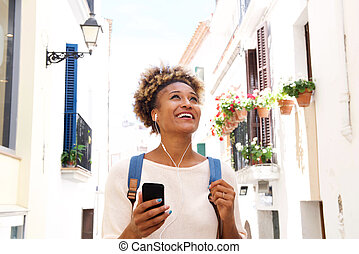 African american woman walking down the street and listening to music on mobile phone