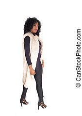 African American woman walking in fur coat.