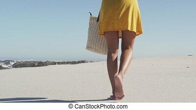 African American woman walking seaside - Rear view low ...