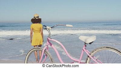 African American woman walking seaside with a bike in ...