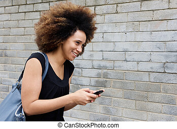 African american woman walking with cellphone
