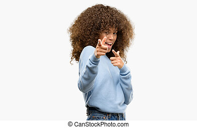 African american woman wearing a sweater pointing fingers to...