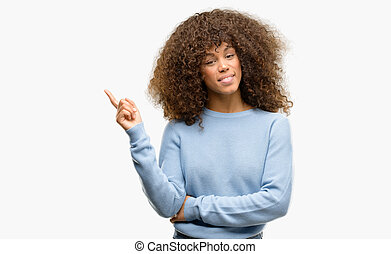 African american woman wearing a sweater with a big smile on face, pointing with hand and finger to the side looking at the camera.