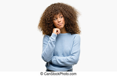 African american woman wearing a sweater with hand on chin thinking about question, pensive expression. Smiling with thoughtful face. Doubt concept.