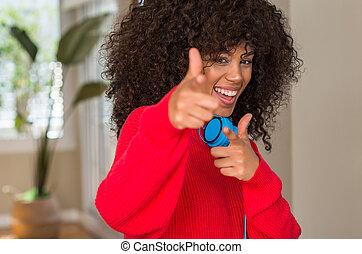 African american woman wearing headphones pointing fingers...