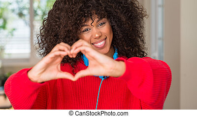 African american woman wearing headphones smiling in love showing heart symbol and shape with hands. Romantic concept.