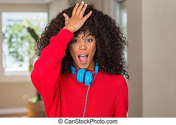 African american woman wearing headphones surprised with...