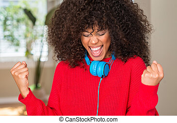 African american woman wearing headphones very happy and excited doing winner gesture with arms raised, smiling and screaming for success. Celebration concept.