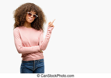 African american woman wearing pink sunglasses with a big smile on face, pointing with hand and finger to the side looking at the camera.
