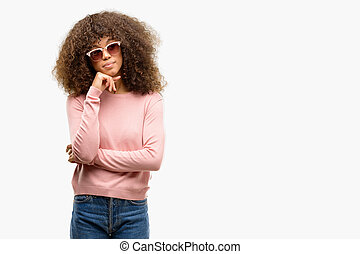 African american woman wearing pink sunglasses with hand on chin thinking about question, pensive expression. Smiling with thoughtful face. Doubt concept.