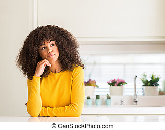 African american woman wearing yellow sweater at kitchen with hand on chin thinking about question, pensive expression. Smiling with thoughtful face. Doubt concept.