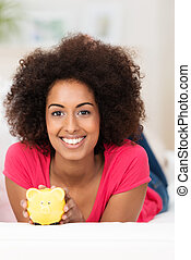 African American woman with a piggy bank
