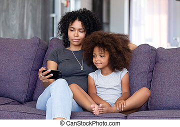 African American woman with daughter using phone together at home