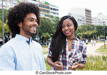 African american woman with dreadlocks flirting with hipster man