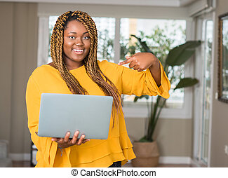 African american woman with laptop with surprise face pointing finger to himself