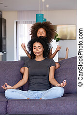 African American woman with little daughter practicing yoga at home