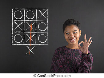 African American woman with perfect hand signal with a tic tac toe diagram on blackboard background
