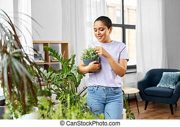 african american woman with plants at home
