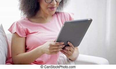 african american woman with tablet pc at home