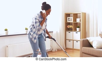 african american woman with vacuum cleaner at home - people,...