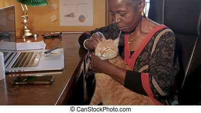 African American woman working at home petting her...