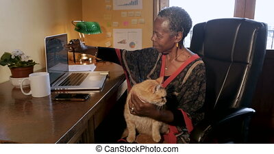 African American woman working from home with a cat on her lap