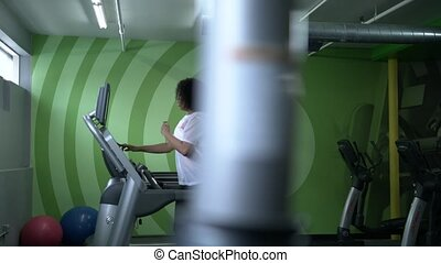 African American woman working on a treadmill in the gym