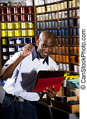 African American worker standing in front of colored inks in print shop