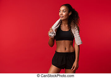 African american young girl 20s in black sportswear with towel over her neck standing, isolated over red background