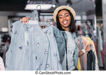 african american young girl in boutique, clothes shopping concept