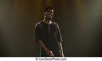 African American young man in national ethnic costume dances with pleasure and sings a song. African folklore performed by a black artist in a dark studio with smoke and yellow light. Live improvised theater concert.