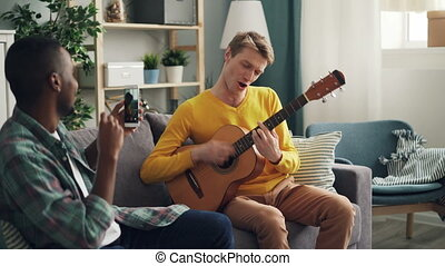African American young man is holding modern smartphone and making video of his Caucasian friend playing the guitar and singing at home. Fun and gadgets concept.