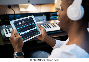 African-american young man with headphones holding tablet ...
