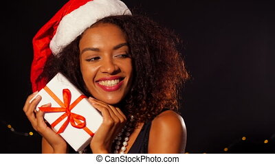 African-american young woman in party dress and Santa hat holding gift box with red ribbon on black background. Girl smiling, she happy to get present on New Year or Christmas.