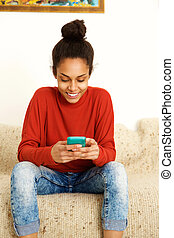 African american young woman using smart phone at home