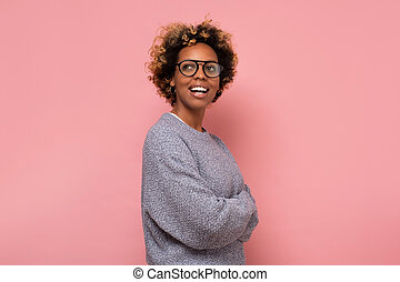 African american young woman with glasses and sweater smiling.