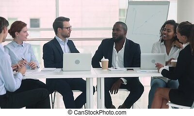African and caucasian businessmen in suits talking at group...